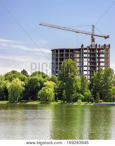 Building Under Construction And Industrial Tower Crane On The Bank Of Big Lake With Green Trees In F