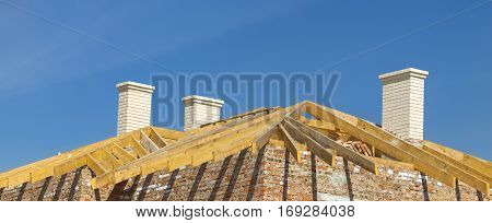 Roofing Construction. Wooden Roof Frame, White Chimneys And Yellow Brick House Construction