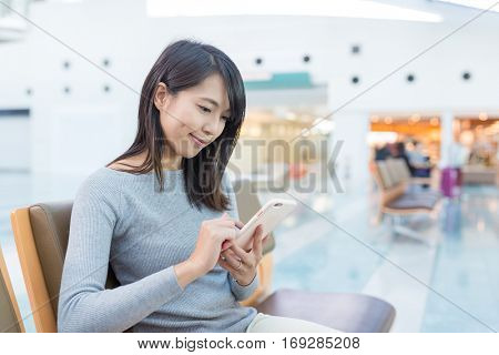Young woman using cellphone in station hall