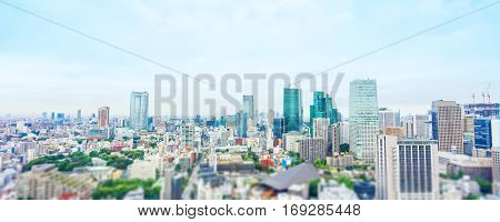Business and culture concept - panoramic modern city skyline bird eye aerial view from tokyo tower under dramatic morning blue cloudy sky in Tokyo Japan. Miniature Tilt-shift effect