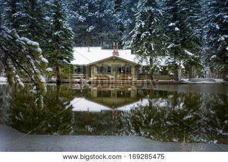 quaint cozy cabin beside a pond in the cold of a snowy morning