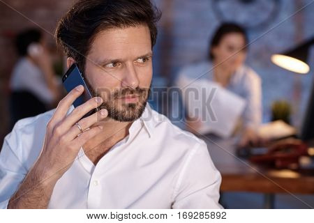 Closeup portrait of businessman talking on mobilephone, looking away.