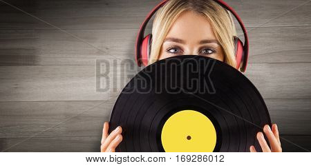 Portrait of a beautiful woman holding a vinyl against wooden flooring