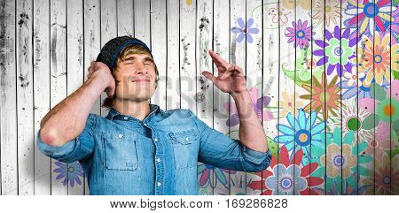 Cheerful hipster listening to music against digitally generated girly floral design