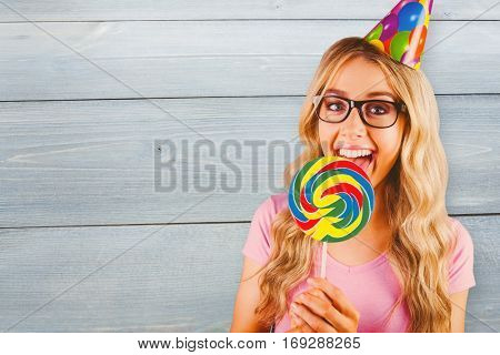 A beautiful hipster holding a giant lollipop against bleached wooden planks background