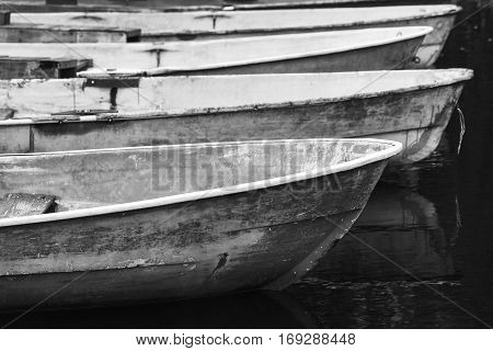 Old Grungy Rowboats Moored In A Row