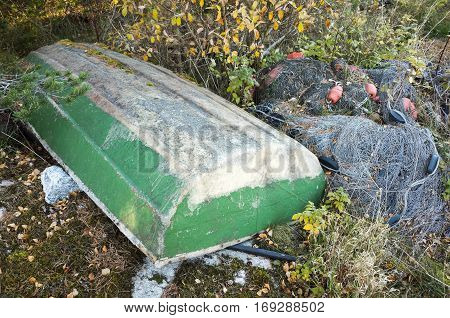 Old Green Rowboat Lays Near Fishing Nets