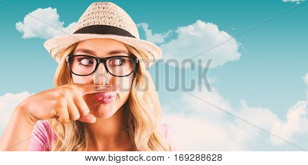 A beautiful hipster having a fake mustache against blue sky