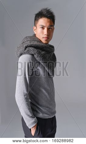 Portrait of young man in scarf on gray background