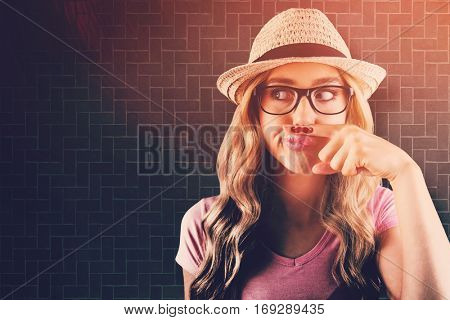 A beautiful hipster having a fake mustache against textured background