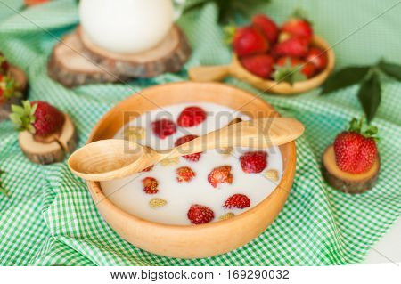 milk with fresh strawberries in a handmade wooden plate with spoon
