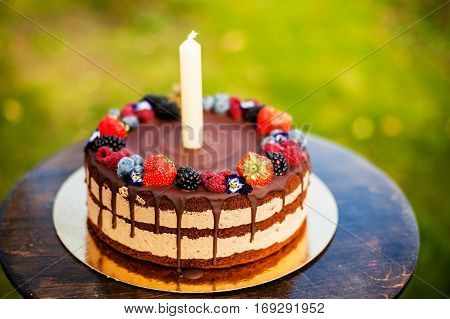 large chocolate and fresh berries birthday cake with a candle