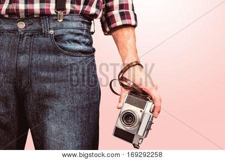 Hipster man holding digital camera against light pink