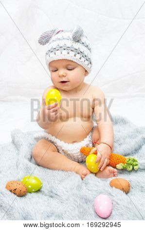 Cheerful baby girl in bunny hat gray blanket with multi colored easter eggs in his hands