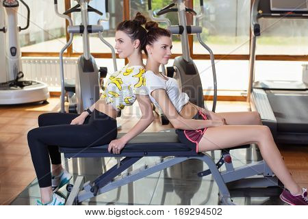 Two twins to play sports in the gym having a rest after exercise resting sitting on a bench. Healthy lifestyle