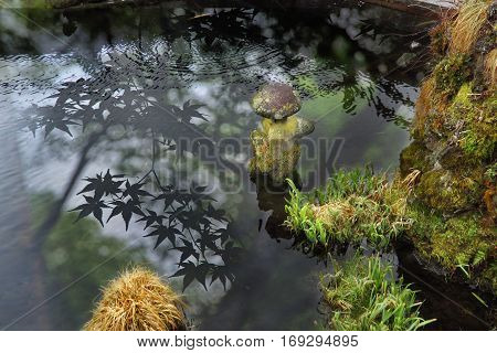Old stone doll in ancient pool with reflection of Japanese maple and rocks with trees up poolside at Yamanashi Japan
