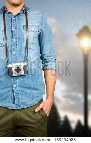 Hipster man holding digital camera against blurred lampposts at night