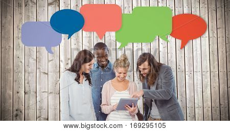 Happy woman holding digital tablet and discussing with coworkers against wooden planks background