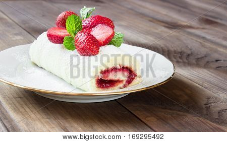 Homemade Sweet roll with Strawberry jam and berries on wooden background. space for text