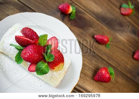 Homemade Sweet roll with Strawberry jam and berries on wooden background