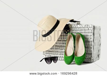 White wicker suitcase womens hat sunglasses and green shoes. Selective focus.