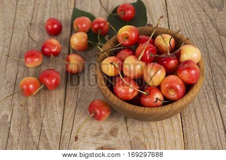 Background of ripe cherries. Pile of fresh and tasty cherries in wooden bowl. Fresh cherries scattered on a wooden table. Top view.