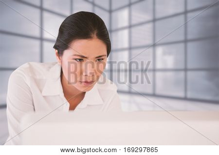 Casual businesswoman concentrating at her desk against cityscape seen through window