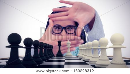 Asian woman making square with hands against white and black pawns facing off with king and queen