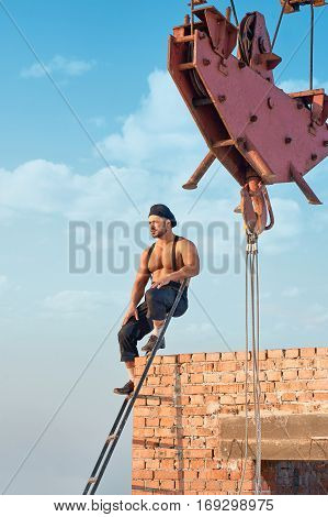 Athletic builder leaning on brick wall and sitting on ladder on high. Male with bare torso in work wear. Iron crane on background. Extreme building in hot weather.