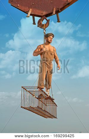 Full length of man holding and standing on iron construction on high at city. Builder wearing hat and work wear looking away and posing. Crane holding construction. Blue sky with clouds on background.
