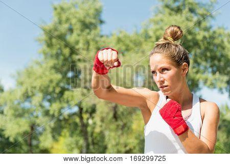 Hook punch on tae bo training, toned image, outdoors