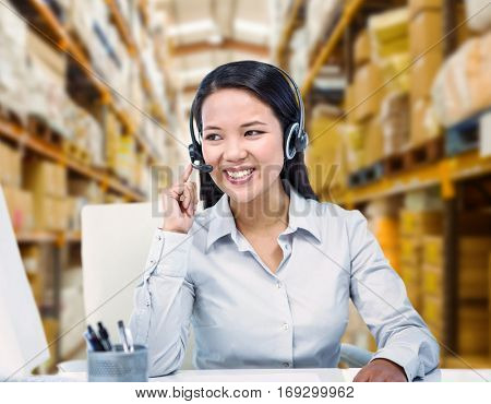 Smiling businesswoman using headset against shelves with boxes in warehouse