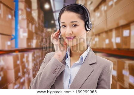 Portrait of a good looking operator posing with a headset against shelves with boxes in warehouse