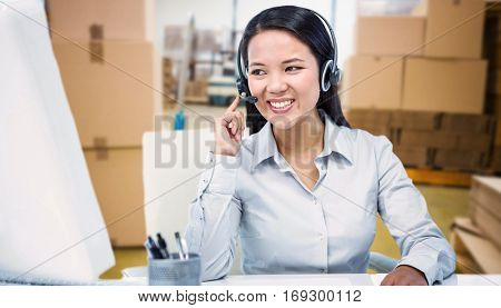 Smiling businesswoman using headset against boxes on trolley in warehouse