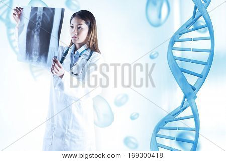 Asian doctor checking MRI scan against blue chromosomes on blue background