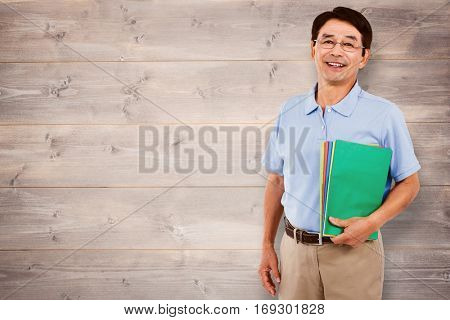 Portrait of happy businessman with files against bleached wooden planks background