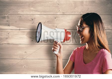 Asian woman shouting in megaphone against bleached wooden planks background