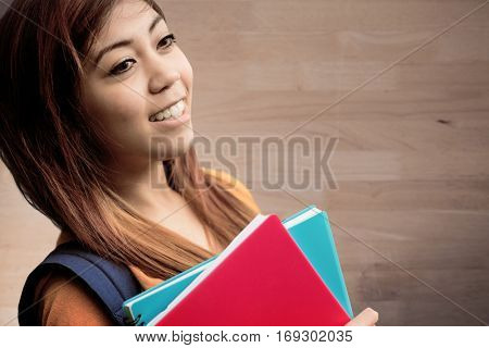 Female college student with books in park against bleached wooden planks background