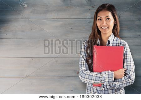 Smiling asian woman holding red book against bleached wooden planks background