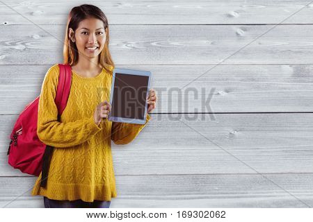 Smiling asian female student showing tablet against bleached wooden planks background