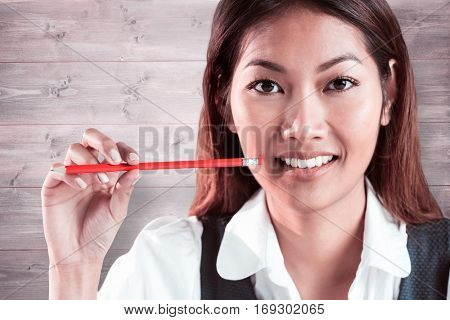 Smiling businesswoman holding a pencil against bleached wooden planks background