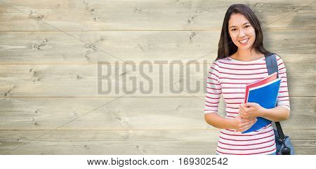 College girl holding books with blurred students in park against bleached wooden planks background