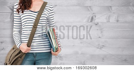 Mid section of man with should bag and files against bleached wooden planks background