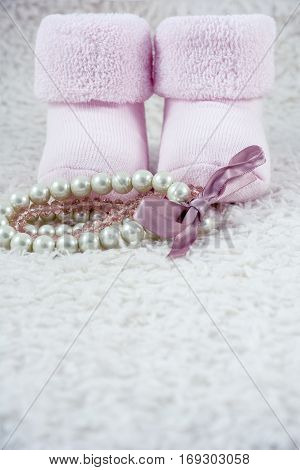 Two pink booties for babies with several bracelets on the white fur