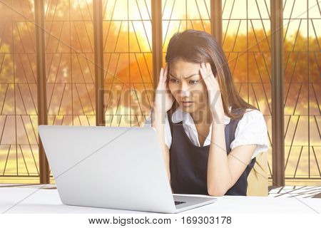 Nervous businesswoman using a laptop against view of a tree