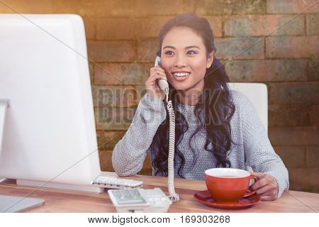 Smiling Asian woman on phone call holding mug against brick wall