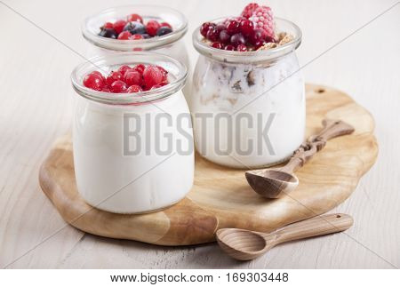 Homemade yogurt with frozen berries red currants black currants raspberries and cranberries in three banks