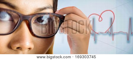 Close up view of a businesswoman holding her eyeglasses against medical background with red ecg line