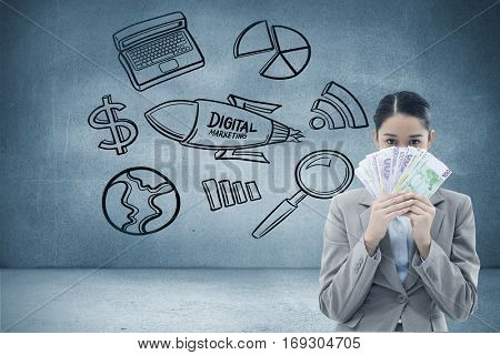 Portrait of a greedy businesswoman holding bank notes against grey room