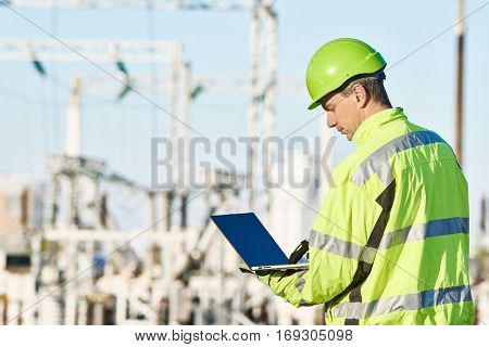 Service engineer working with laptop at heat electric power stat